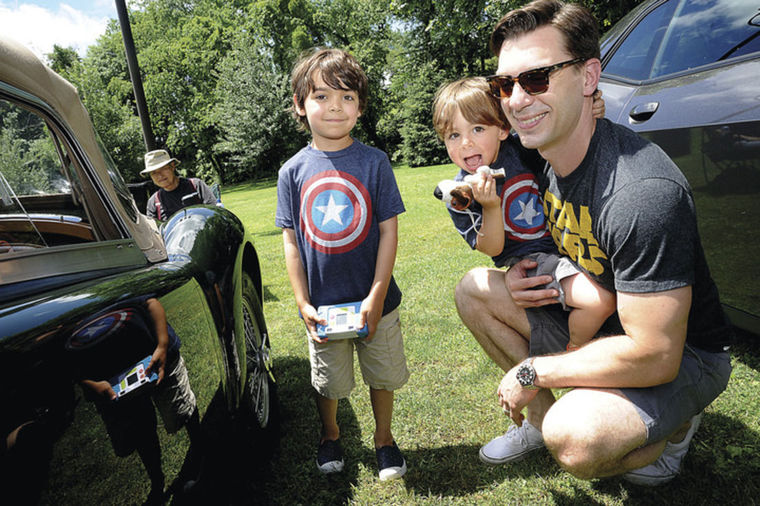 Jon Hammond with his sons Ben 6 and Dylan 2 enjoy the New England Auto Museum's Father's Day car show Sunday at Mathews Park.