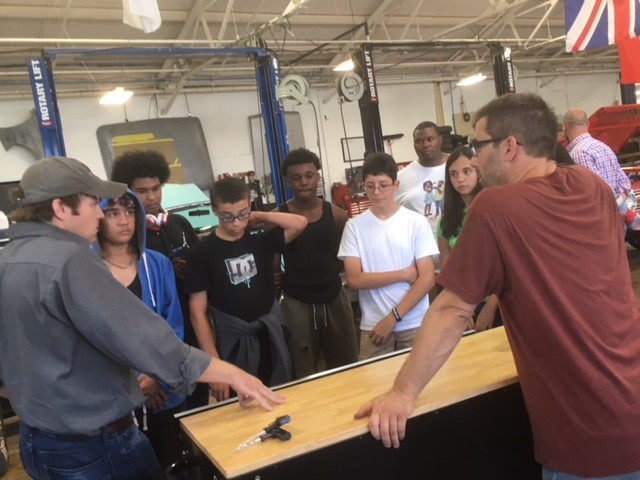 Scott Gilbert and Stan Diguiseppi Jr. talking to BMHS students about the importance of the mechanic's toolbox at Black Bridge Motors' shop in South Norwalk