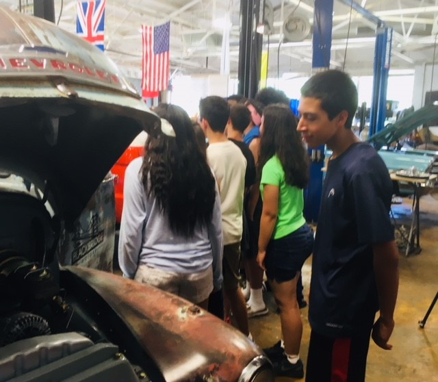 BMHS Auto Technology class student admiring Black Bridge Motor's shop truck equipped with a 550 hp Corvette LT-1 power plant